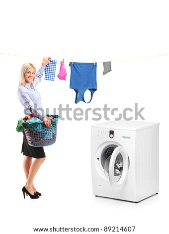 Young smiling woman hanging clothes on clothes line next to a washing machine isolated on white background - stock photo