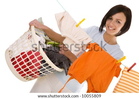 Young smiling woman hanging clothes on clothesline using clothespin. She holding clothes hamper in hands. Front view, looking at camera. White background. - stock photo