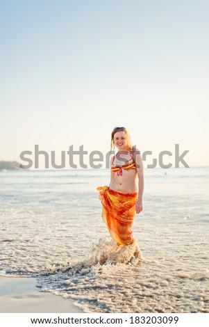 Young smiling woman having fun standing in sea water  - stock photo