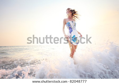 Young smiling woman having fun standing in sea water - stock photo