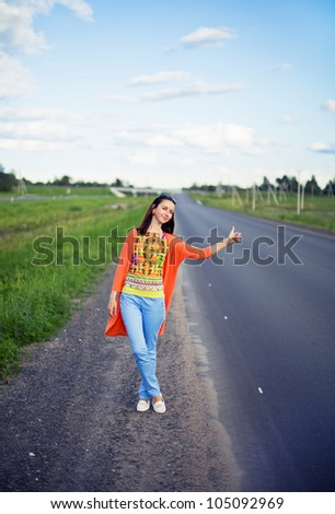 young smiling woman hitch-hiking on a road - stock photo
