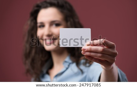 Young smiling woman holding a blank business card - stock photo