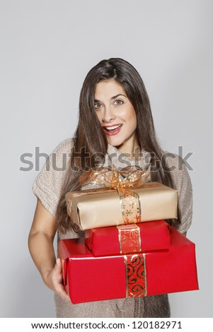 young smiling woman holding Christmas gifts. - stock photo