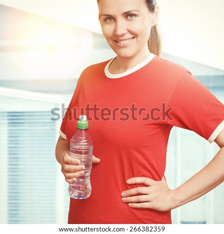Young smiling woman holding cold water bottle