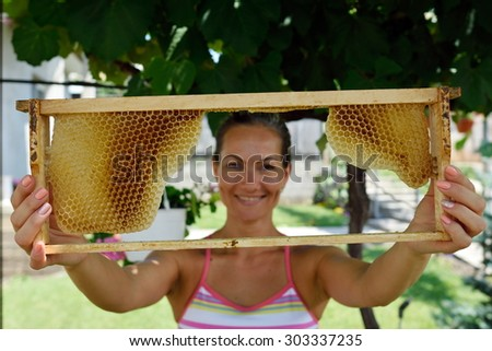 young smiling woman holding frame with honeycomb - stock photo