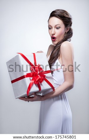 Young smiling woman holding gift - stock photo