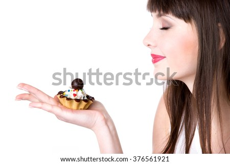Young smiling woman holding in her palm delicious tart cake with cream and chocolate, beautiful cheerful female teen model enjoying smell of the food, studio, white background, copyspace - stock photo