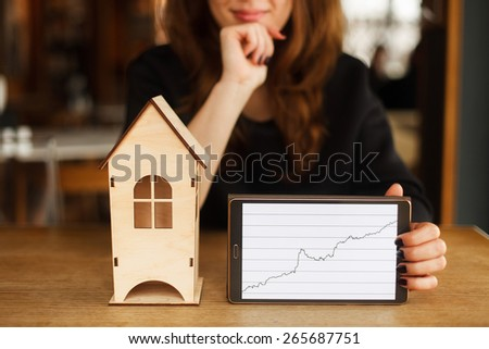 Young smiling woman holding model of house and digital tablet with diagram - stock photo
