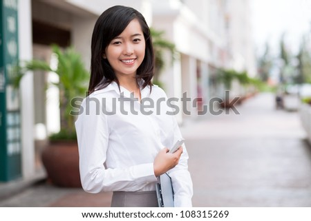 Young smiling woman holding phone and document looking at camera - stock photo