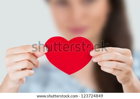 Young smiling woman holding red heart. Focus on heart