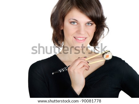 Young smiling woman holding sushi with chopsticks - stock photo