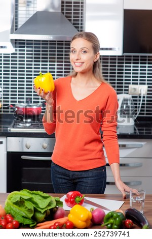 Young smiling Woman holding yellow pepper cooking in new kitchen making healthy food with vegetables.  - stock photo