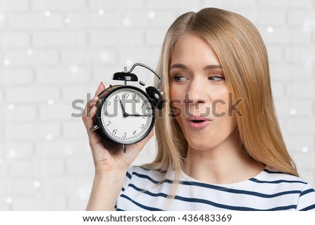 Young smiling woman holds black clock