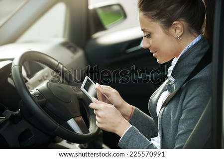 Young smiling woman in a car using a touch screen digital tablet.