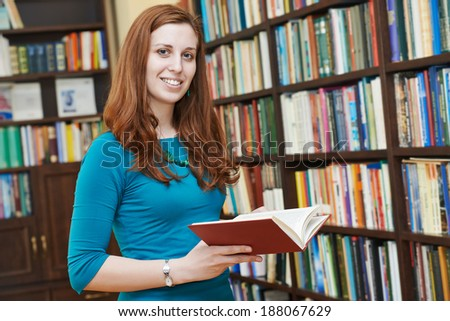 Young smiling woman in a library with book at self-education