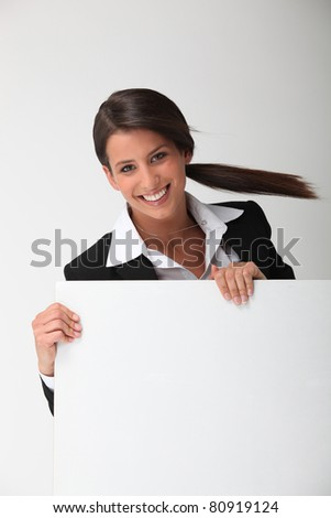 Young smiling woman in a suit with a board blank for your message - stock photo