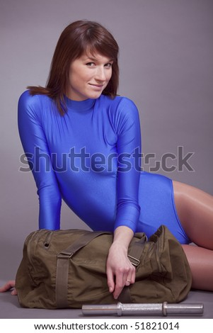 young smiling woman in blue leotard sitting on the ground