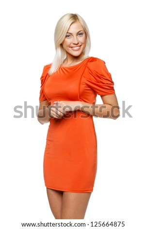 Young smiling woman in bright orange dress, over white background - stock photo