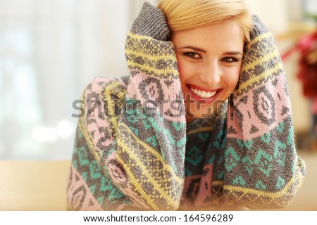 Young smiling woman in colourful sweater at home - stock photo