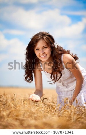 Young smiling woman in golden wheat field