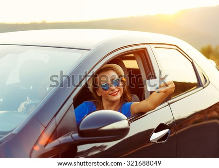 Young smiling woman in hat and sunglasses making self portrait sitting in the car
