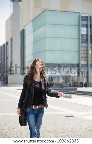 Young smiling woman in hurry - walking street with notebook bag