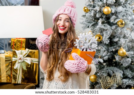 Young smiling woman in knitted hat and gloves holding shopping bag with snow flake and credit card standing in decorated with Christmas tree home interior. Winter holiday shopping concept