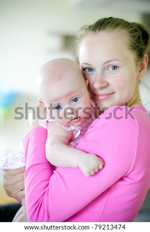 young smiling woman in pink clothes holding her little daughter - stock photo