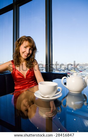 Young smiling woman in red dress sitting at cafe