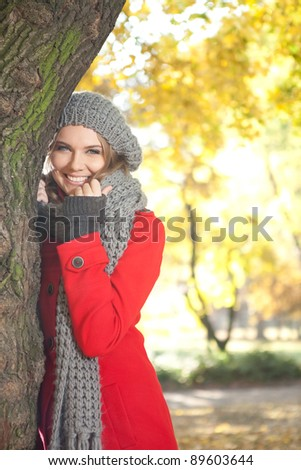 young smiling woman in season warm clothing in autumn park - stock photo