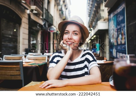 Young smiling woman in striped shirt resting in open-terrace restaurant situated on a beautiful european street in Italy - stock photo