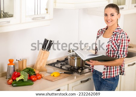 Young, smiling woman in the kitchen while cooking dinner. - stock photo