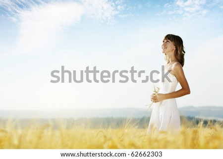 Young smiling woman in white dress in field with wheat - stock photo