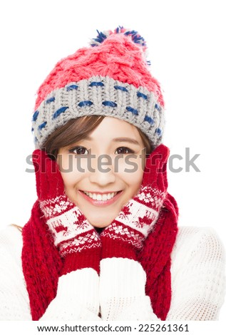 young smiling woman in winter clothes and touching face - isolated on white background