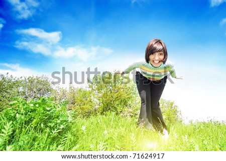 Young smiling woman into the field against the blue sky - stock photo
