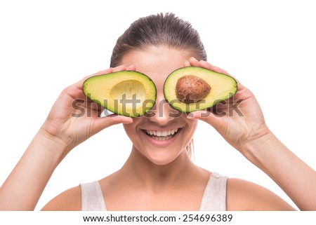 Young, smiling woman is holding avocado in front of her eyes on white background. - stock photo
