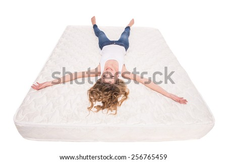 Young, smiling woman is lying on the quality mattress over white background. - stock photo