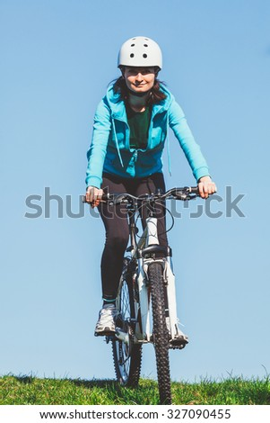 Young smiling woman is riding a bike on a green field in a sunny day