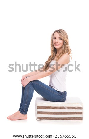 Young, smiling woman is sitting on the quality mattress over white background. - stock photo