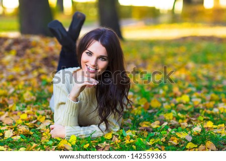 Young smiling woman laying on yellow leaves in a park - stock photo
