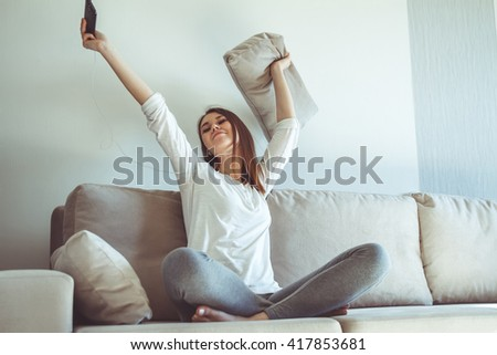 Young smiling woman listening to music while sitting on the couchGirl having fun and dancing, listening to music while sitting on the couch - stock photo