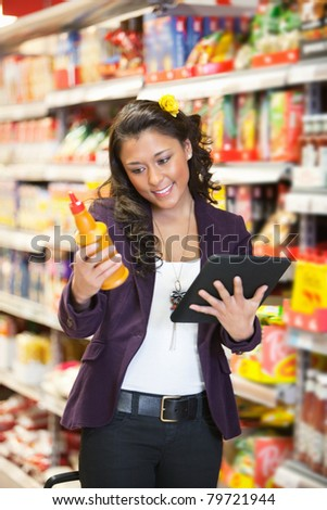 Young smiling woman looking at a product while holding digital tablet in shopping centre - stock photo