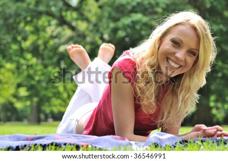 Young smiling woman lying on rug in grass during sunny day (park - outdoors) - stock photo