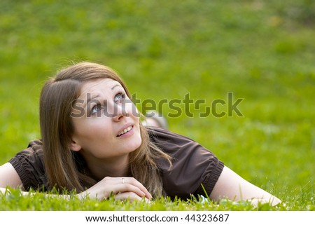 Young smiling woman lying on the grass in the park