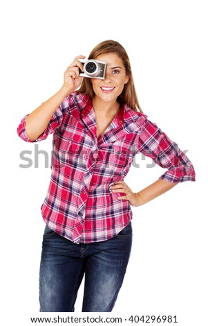 Young smiling woman making a photo through old photo camera - stock photo