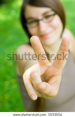 young smiling woman making victory gesture