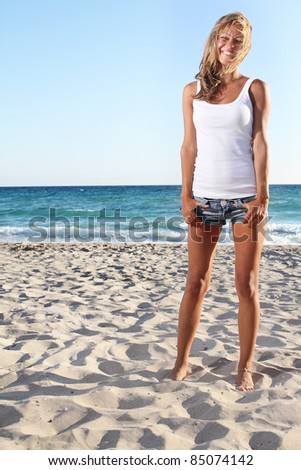 young smiling woman on sand beach - stock photo