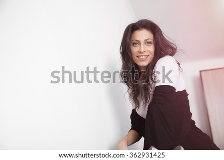 Young smiling woman on the sofa at home in white lit room against the window. Smooth morning light, casual style - concept of happy family living and lifestyle - stock photo