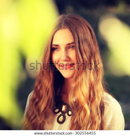 Young smiling woman outdoors portrait. Soft sunny colors.Close portrait. - stock photo