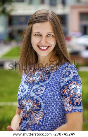 Young smiling woman outdoors portrait. Soft sunny colors.Close portrait. Summer portrait of a beautiful young brunette Caucasian girl with straight hair in blue dress outdoors in the city - stock photo